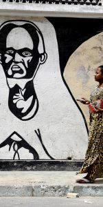 A man walks in front a mural painting of Cheikh As-Saidi Al Hadji Malick Ibn Uthman Ibn Demba Ibn Chamsidine SY, a scholar of the Maliki school of Law and of the Ash'arite theology school, as well as an imam of the Sufi brotherhood Tidjane, on June 29, 2015 in Dakar. Graffiti featuring religious figures, politicians, daily life scenes, as well as Ebola and malaria prevention messages cover the walls of certain streets of Dakar. Written in French or in Wolof, these messages can have educational purposes while others merely contribute to embellish the capital.  AFP PHOTO / SEYLLOU / AFP PHOTO / SEYLLOU
